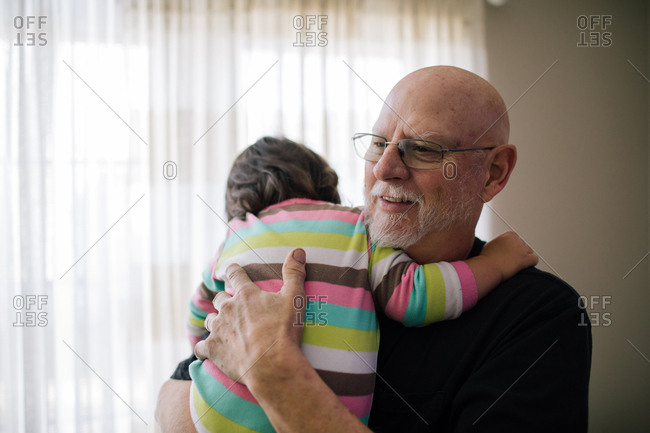 Grandfather holding toddler girl in striped pajamas