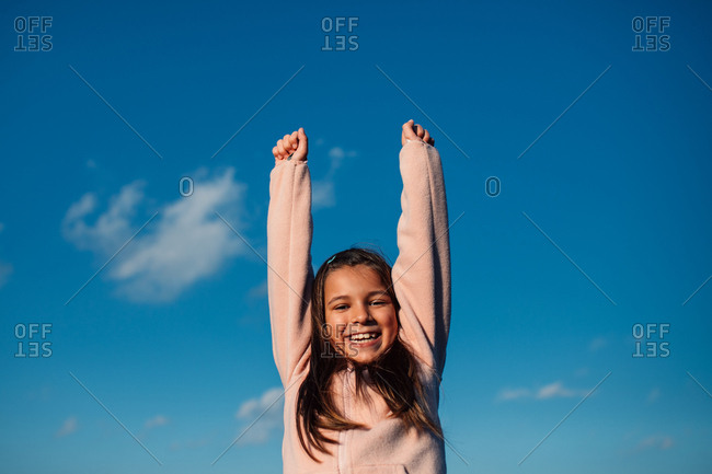 Happy little girl holding her arms in the air