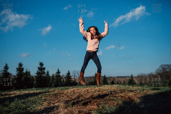 Happy little girl jumping with her arms in the air