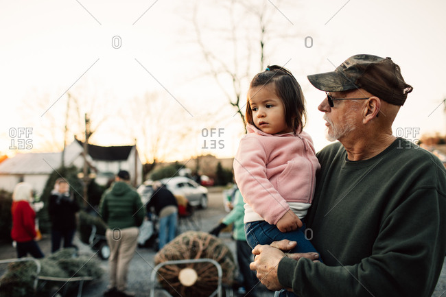 Grandfather holding toddler girl on a tree farm