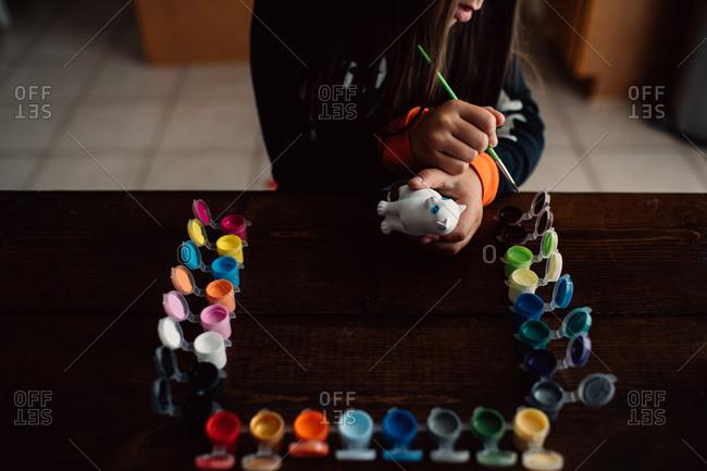 Girl painting ceramic cat
