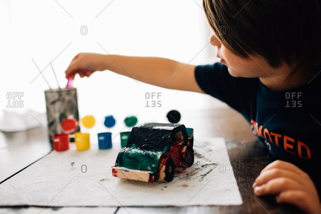 Young boy painting wooden car