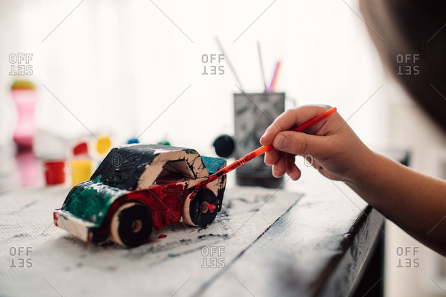 Boy painting wooden car