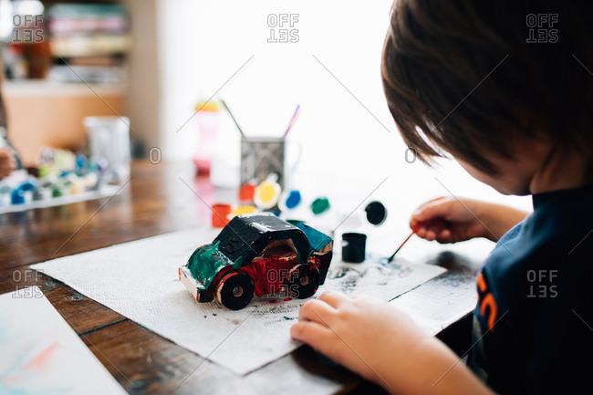 Little boy painting wooden car