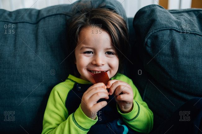 Happy boy eating snack on sofa