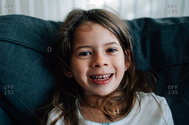 Portrait of a smiling young girl sitting on sofa