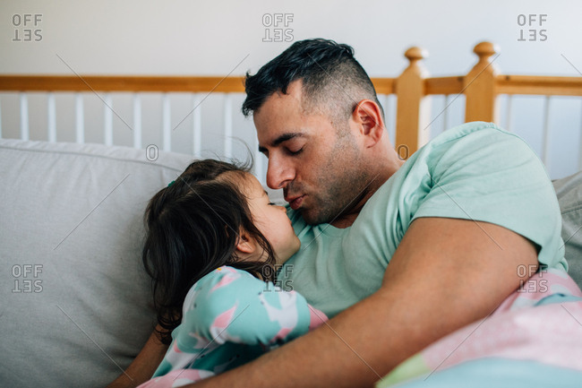 Father giving little girl a kiss in bed