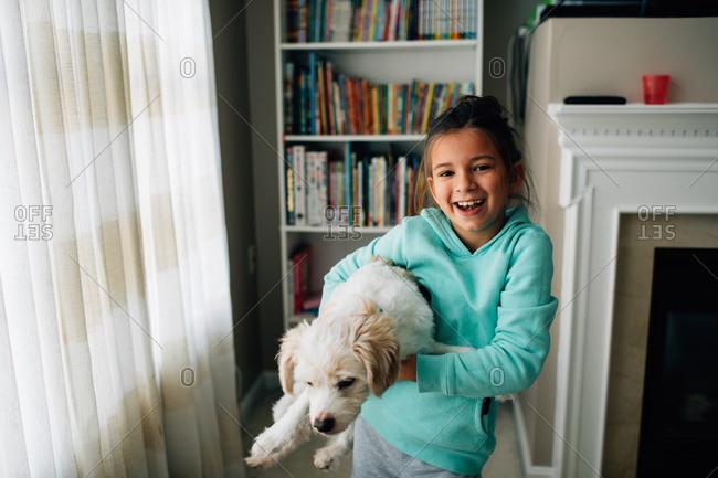Little girl holding fluffy dog