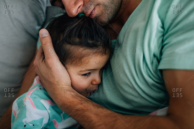 Father cuddling with little girl in bed