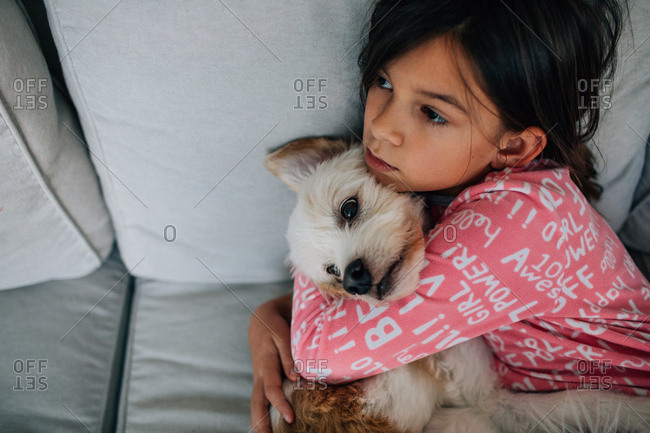 Girl cuddling with dog on sofa