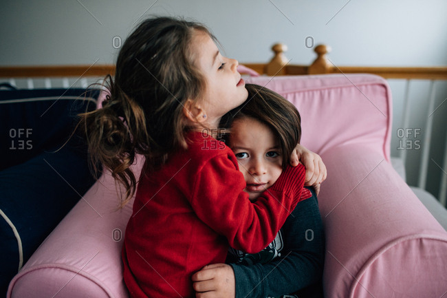 Two kids hugging on pink chair