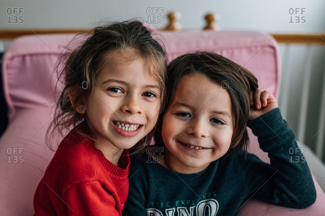 Portrait of two happy kids on pink chair