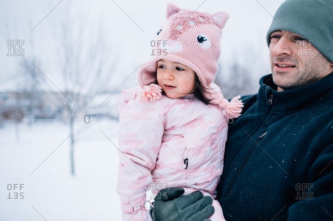 Father holding toddler daughter outdoors in winter
