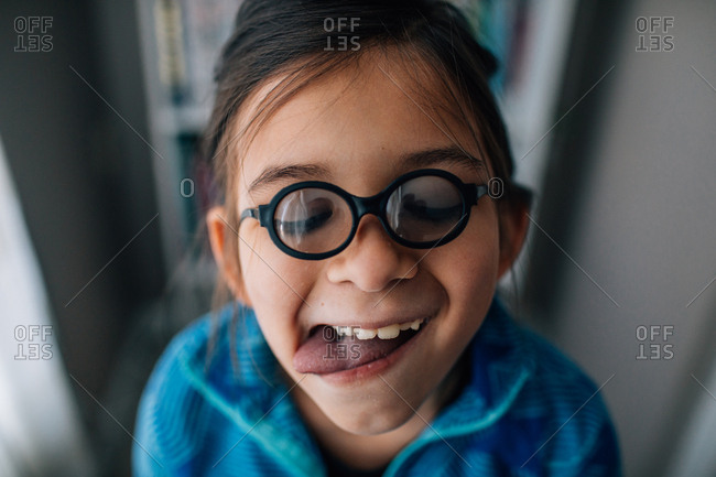 Portrait of a goofy young girl wearing tiny glasses and sticking tongue out