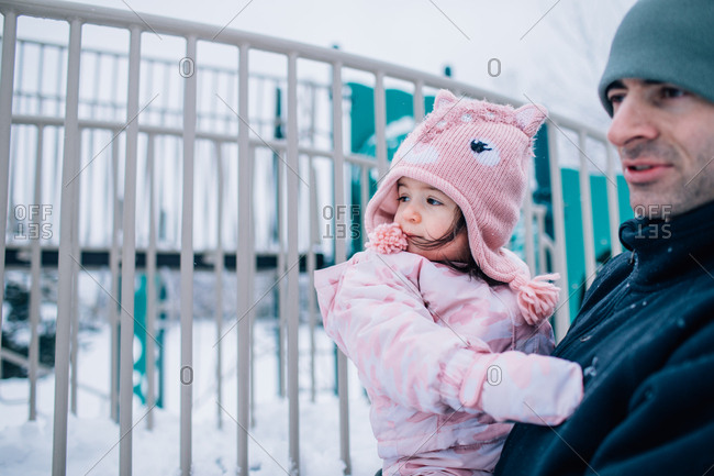 Father holding toddler daughter at a park in winter