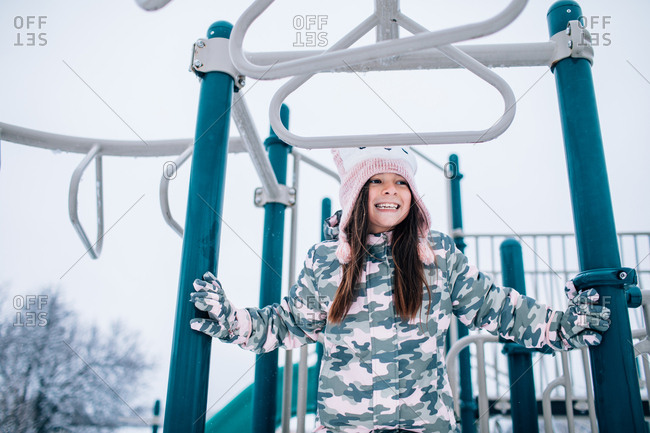 Little girl playing on playground in winter