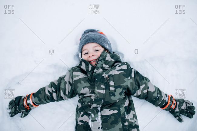 Young boy making snow angle