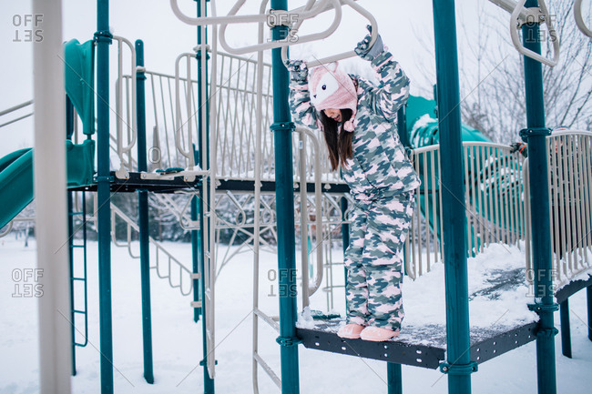 Little girl playing on playground equipment in winter