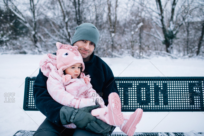 Father holding toddler daughter on a park bench in winter