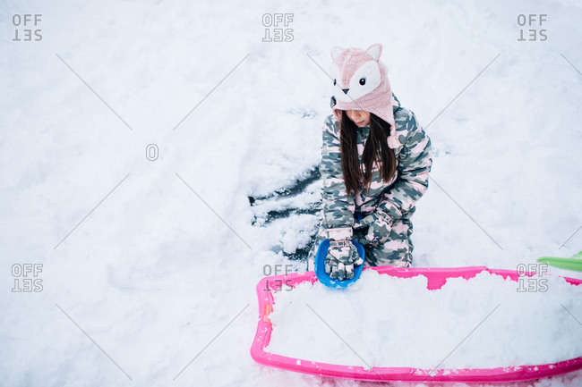 Little girl filling sled with snow