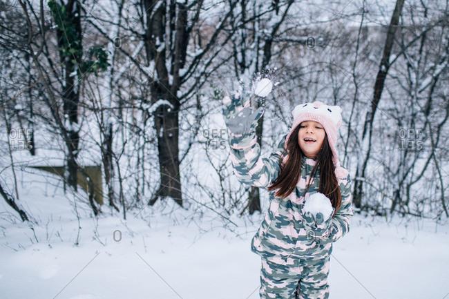 Little girl throwing a snowball