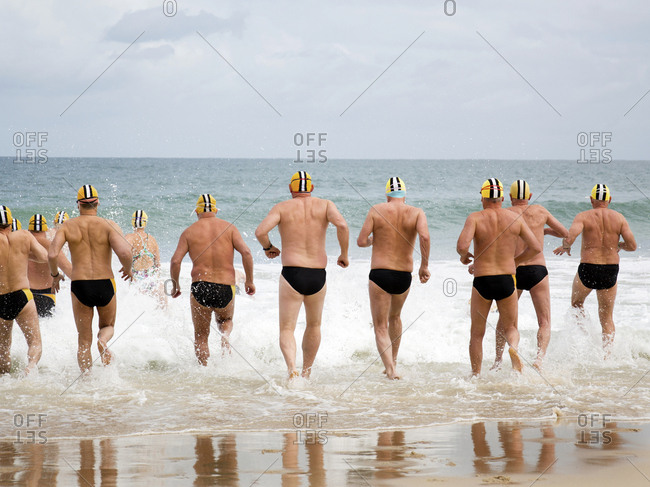 Swimming club entering the water on Clottesloe beach, Perth, Australia