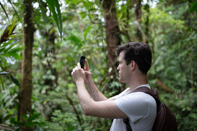 Man taking pictures with Smartphone in the rainforest