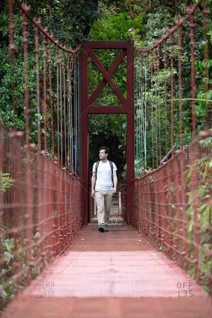 Man walking on footbridge through the rainforest