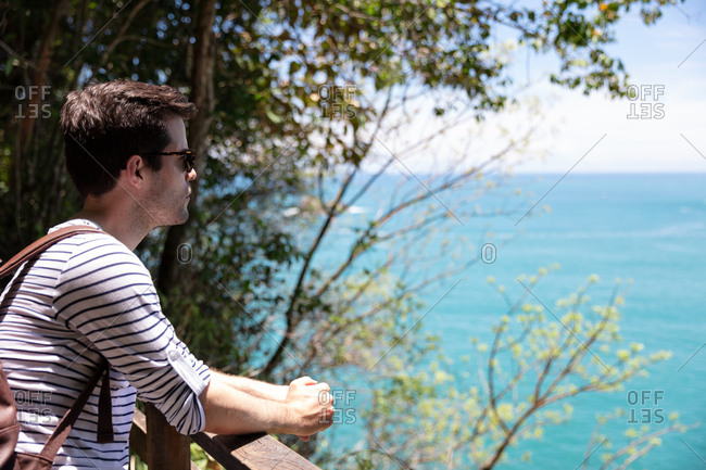 Young man looking out at ocean while hiking in Costa Rica