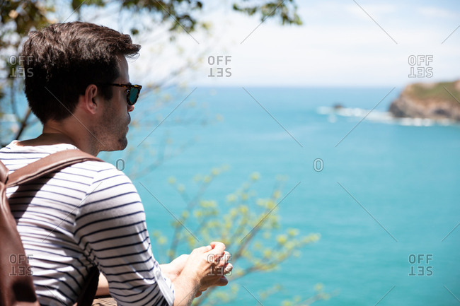 Man looking out at ocean while hiking in Costa Rica