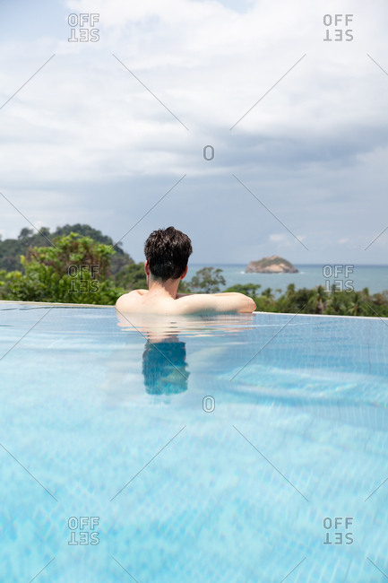 Man swimming in infinity pool on summer holiday
