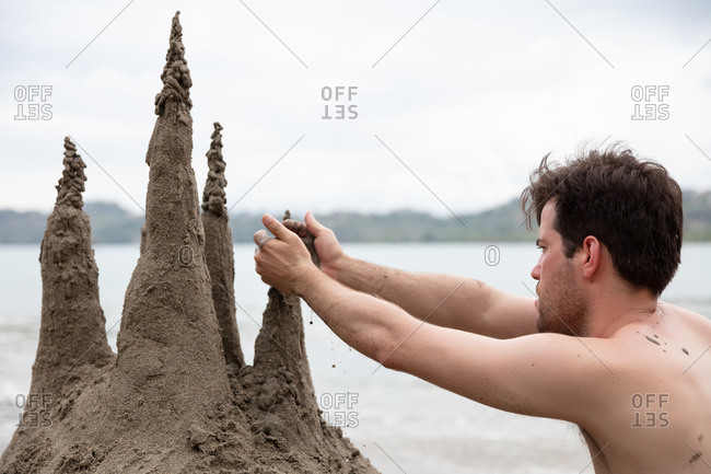 Man building a sandcastle on the coast of Costa Rica