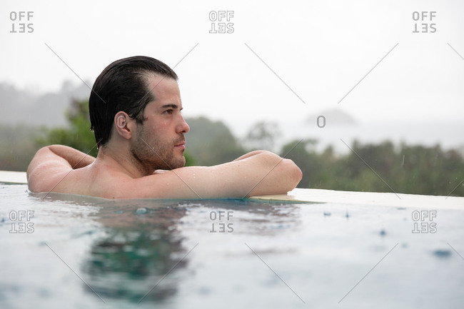 Man in infinity pool whilst raining