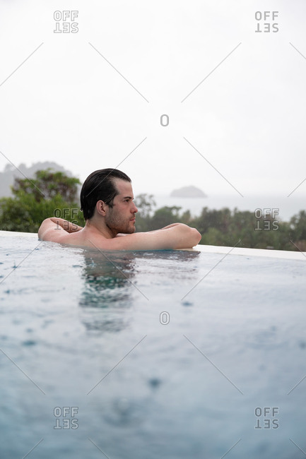 Man swimming in infinity pool whilst raining