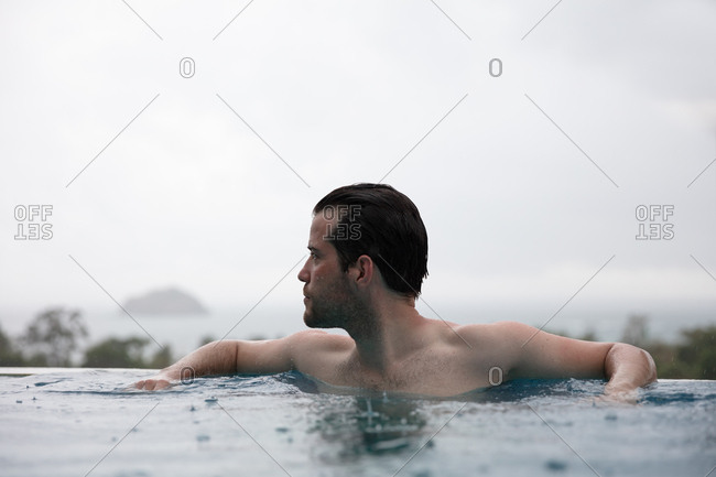 Man swimming in infinity pool during the rain