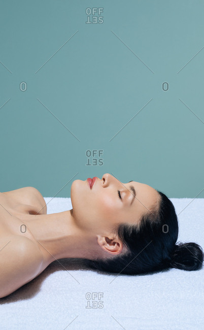 Beautiful Caucasian woman lying on massage table waiting for spa treatment.