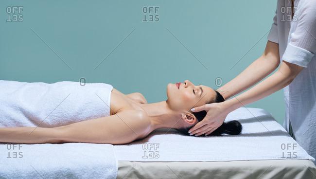 Beautiful young Caucasian woman enjoying head massage.