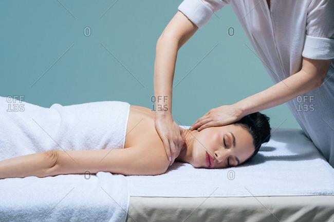 Beautiful young Caucasian woman enjoying neck massage at salon.