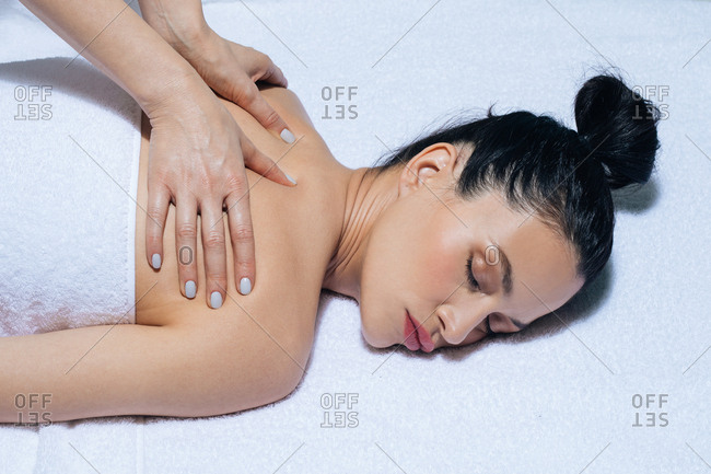 Beautiful young Caucasian woman enjoying back massage at salon.