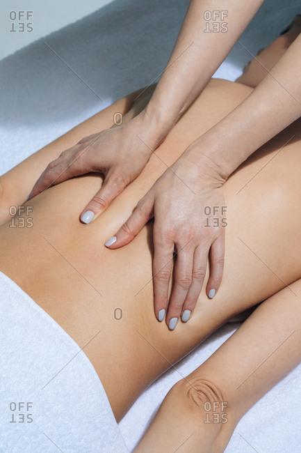 Hands of unrecognisable woman masseur doing back massage at salon.