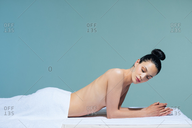 Beautiful Caucasian woman relaxing on massage table at wellness salon.