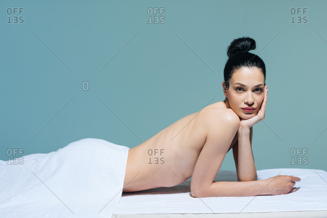 Portrait of beautiful naked Caucasian woman brunette lying on massage table at salon and looking at camera.