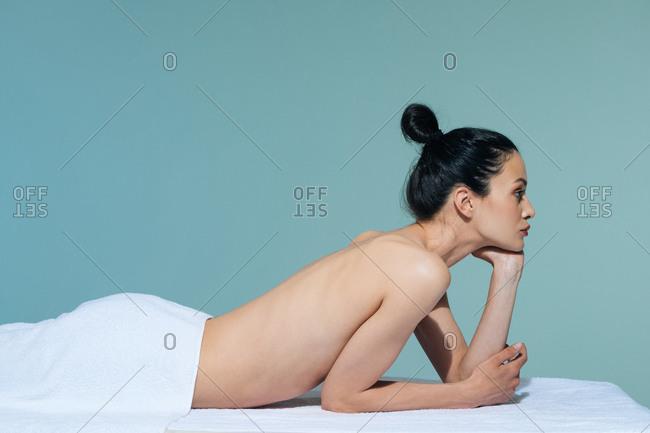 Portrait of beautiful naked Caucasian woman brunette lying on massage table at salon.