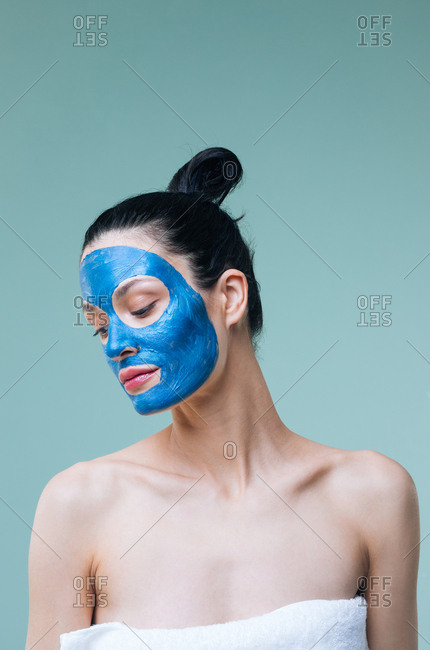 Portrait of pretty Caucasian woman brunette with blue clay cosmetic face mask.