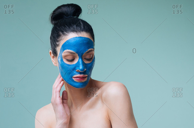 Portrait of beautiful Caucasian woman brunette with blue clay cosmetic face mask.