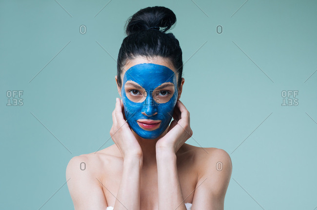 Portrait of pretty Caucasian woman brunette with blue clay cosmetic face mask looking at camera.