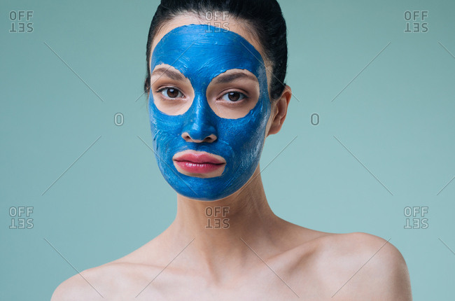 Studio portrait of beautiful Caucasian woman brunette with blue clay face mask looking at camera.