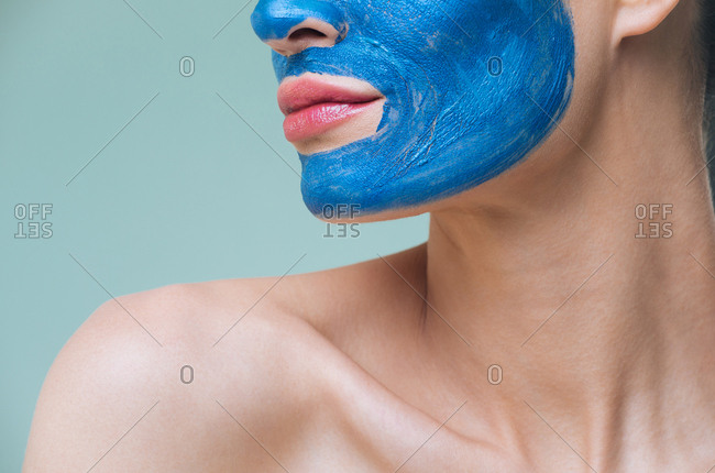 Unrecognisable woman posing with blue clay cosmetic face mask.