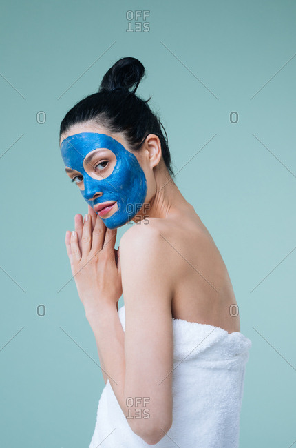 Beautiful Caucasian woman model posing with blue face cosmetic mask and towel.