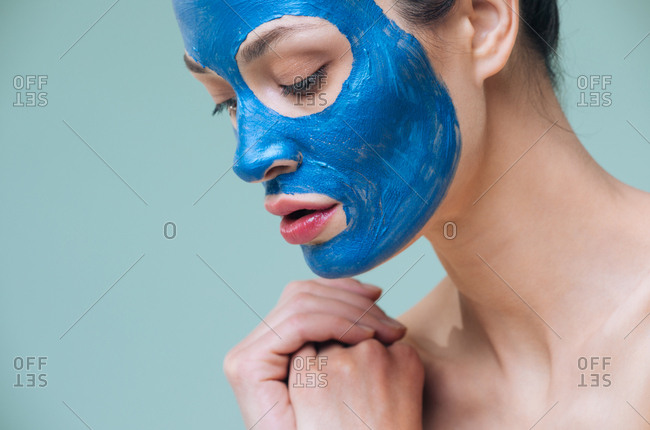 Studio portrait of  Caucasian woman model posing with blue clay mask on her face.
